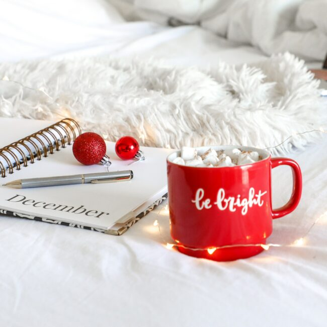 red ceramic mug on white mat beside notebook ... making Christmas traditions